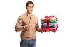 Hombre joven que sostiene una pila de ropa y de punto planchados y llenos Fotografía de archivo