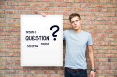 Hombre joven que sostiene whiteboard con problemas de la solución Imagen de archivo libre de regalías