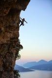 Hombre joven que sube el acantilado vertical en la puesta del sol Fotos de archivo