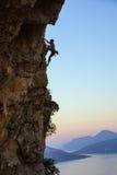 Hombre joven que sube el acantilado vertical en la puesta del sol Imagen de archivo libre de regalías
