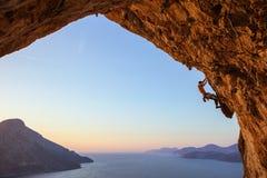 Hombre joven que sube en cueva Fotografía de archivo