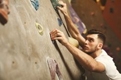 Hombre joven que sube la pared artificial de la roca en el gimnasio Imagen de archivo libre de regalías