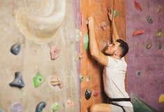 Hombre joven que sube la pared artificial de la roca en el gimnasio Fotos de archivo