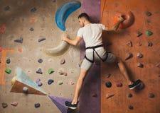 Hombre joven que sube la pared artificial de la roca en el gimnasio Imágenes de archivo libres de regalías