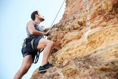 Hombre joven que sube la pared rocosa natural Imagenes de archivo