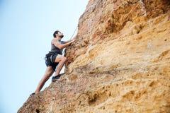 Hombre joven que sube la pared rocosa natural Fotografía de archivo