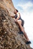 Hombre joven que sube la pared rocosa natural Fotografía de archivo libre de regalías