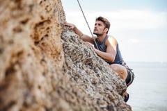 Hombre joven que sube la pared rocosa natural Fotos de archivo