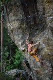 Hombre joven que sube la pared vertical con el bosque en el fondo Foto de archivo