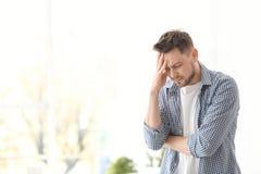 Hombre joven que sufre de dolor de cabeza Foto de archivo libre de regalías
