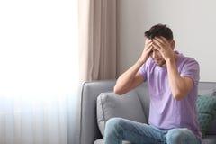 Hombre joven que sufre de dolor de cabeza Imagenes de archivo