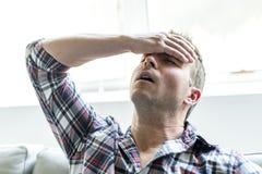 Hombre joven que sufre de dolor de cabeza en casa Fotos de archivo libres de regalías
