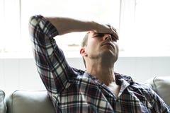 Hombre joven que sufre de dolor de cabeza en casa Imágenes de archivo libres de regalías