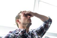 Hombre joven que sufre de dolor de cabeza en casa Fotos de archivo