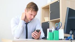 Hombre joven que sufre de dolor de cuello mientras que trabaja en el ordenador 4k, cámara lenta almacen de video