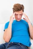 Hombre joven que sufre de dolor de cabeza Imágenes de archivo libres de regalías