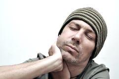 Hombre joven que sufre del dolor de muelas, dolor de dientes, teniendo un hinchado Foto de archivo