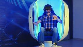 Hombre joven que sumerge en la experiencia de la realidad virtual que se sienta en una silla móvil Imágenes de archivo libres de regalías