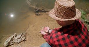 Hombre joven que sumerge las manos en el lago Imagenes de archivo