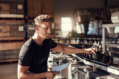 Hombre joven que supervisa el proceso del embotellamiento de la cerveza imagen de archivo