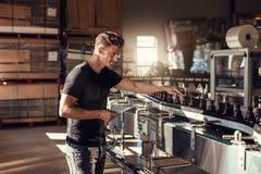 Hombre joven que supervisa la producción de la cerveza en la cervecería imagenes de archivo