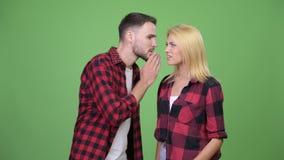 Hombre joven que susurra a la mujer joven y que parece descontentado almacen de video