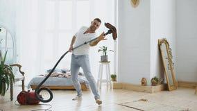 Hombre joven que tiene casa de la limpieza de la diversión con el baile del aspirador foto de archivo