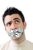 Hombre joven que tiene cinta gris del conducto en su boca Fotos de archivo