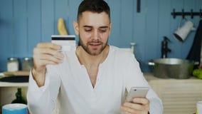 Hombre joven que tiene compras en línea usando tarjeta de crédito y smartphone mientras que desayune en la cocina en casa almacen de video