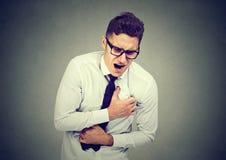 Hombre joven que tiene dolor de pecho, ataque del corazón foto de archivo