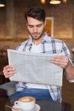 Hombre joven que tiene taza de periódico de la lectura del café Imágenes de archivo libres de regalías
