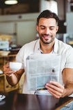 Hombre joven que tiene taza de periódico de la lectura del café Foto de archivo