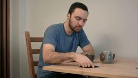 Hombre joven que tiene una llamada de teléfono urgente en el medio del desayuno