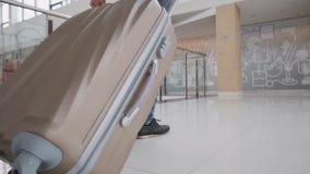 Hombre joven que tira de la maleta en terminal de aeropuerto moderno El individuo que viaja que lleva estilo sport elegante viste almacen de video