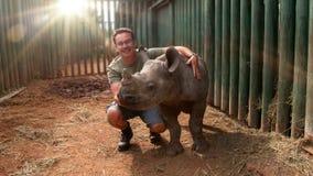 Hombre joven que toca al bebé del rinoceronte fotos de archivo libres de regalías