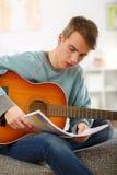 Hombre joven que toca la guitarra acústica Imágenes de archivo libres de regalías