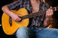 Hombre joven que toca la guitarra acústica Imagen de archivo libre de regalías