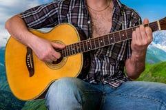Hombre joven que toca la guitarra acústica Fotografía de archivo