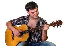 Hombre joven que toca la guitarra acústica - aislada en blanco Foto de archivo