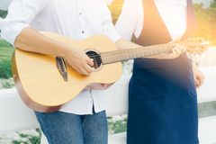 Hombre joven que toca la guitarra acústica con la novia Imagen de archivo