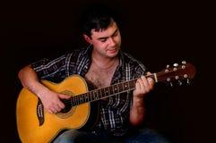 Hombre joven que toca la guitarra acústica - en negro Imágenes de archivo libres de regalías