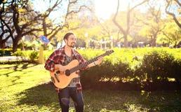 Hombre joven que toca la guitarra baja acústica en el parque Fotos de archivo libres de regalías