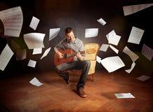 Hombre joven que toca la guitarra con el vuelo de la partitura alrededor de él Fotos de archivo libres de regalías