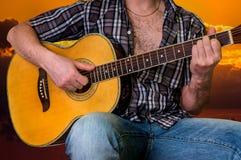 Hombre joven que toca la guitarra en la puesta del sol Foto de archivo libre de regalías