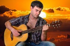 Hombre joven que toca la guitarra en la puesta del sol Imagen de archivo