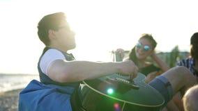 Hombre joven que toca la guitarra entre el grupo de amigos que se sientan en easychairs en la playa y que cantan en una tarde del metrajes