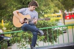 Hombre joven que toca una guitarra Foto de archivo libre de regalías