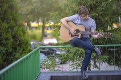 Hombre joven que toca una guitarra Imagenes de archivo