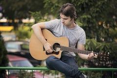 Hombre joven que toca una guitarra Foto de archivo