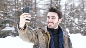 Hombre joven que toma el selfie en nieve almacen de video